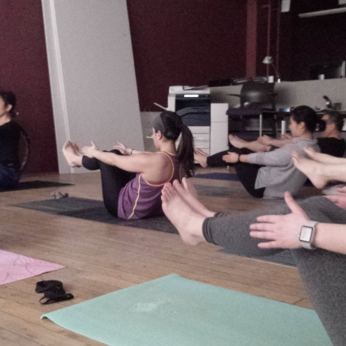 Our team unified in Navasana (Boat Pose) while Pam guides us through the position and our breathing.